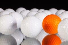 Lonely orange golf ball between white golf balls. Golf balls on the black glass table Stock Photos