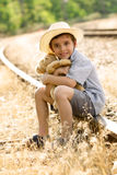 Lonely orphan child sitting on the railroad Royalty Free Stock Photography