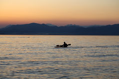 Lonely paddler on the lake during the sunset. Lonely paddler on the lake during the sunset Royalty Free Stock Photography