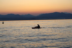 Lonely paddler on the lake during the sunset.  Stock Photo