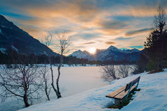 Lonely park bench at sunset in alps Royalty Free Stock Image