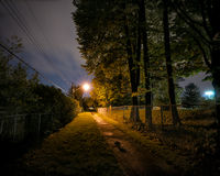 Lonely Path at Night. A lonely, deserted and spooky treed pathway at night time in a city park Royalty Free Stock Image