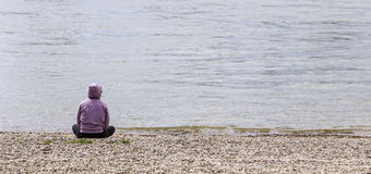 Lonely person on beach. A lonely person sitting on the beach by the sea stock photos