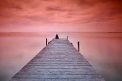 Lonely person sitting on pier Royalty Free Stock Photos