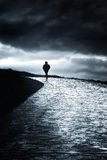 Lonely person walking. With clouds Royalty Free Stock Image