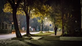 Lonely person walking by the empty street at night royalty free stock photography