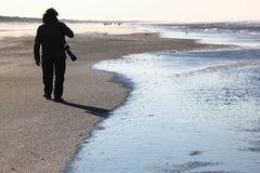 Lonely photographer at Ameland Island, Netherlands. Ameland is one of the West Frisian Islands off the north coast of the Netherlands. It consists mostly of sand Royalty Free Stock Photography