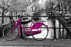 Lonely pink bike in Amsterdam. A picture of a lonely pink bike on the bridge over the channel in Amsterdam. The background is black and white stock image