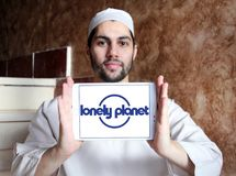 Lonely Planet logo. Logo of Lonely Planet on samsung tablet holded by arab muslim man. Lonely Planet is the largest travel guide book publisher in the world royalty free stock images