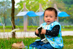Lonely play mobile phone baby(Asia, China, Chinese) Stock Photography