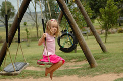 Lonely playground. A full body of a beautiful little blond caucasian lonely girl child with sceptical and scared expression in the pretty face sitting on the Stock Photo
