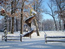 Lonely Playground. Empty playgrounds always make for interesting pictures. Vacant curly-q slide after the snow Stock Photos