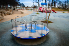 Lonely Playground. Empty playground with a spinning merry go round royalty free stock photos