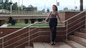 Lonely pretty girl female standing on stairs wind flowing hair in a city street. Lonely pretty girl female in dress standing on stairs wind flowing hair in cool stock video