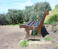 A lonely public park on a beautiful spring day. a wooden bench rests in the green garden next to an olive grove. on one side stock images