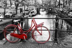 Lonely red bike on the bridge. A picture of a lonely red bike on the bridge over the channel in Amsterdam. The background is black and white Royalty Free Stock Images