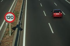 Lonely red car on highway and SPEED LIMIT sign in Madrid. Lonely red car passing through multi lane highway and SPEED LIMIT signpost, on sunset in Madrid stock photos