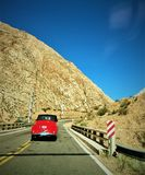 Lonely red car on the road. Andes mountains, Argentina. Road takes you to Mendoza. On the way to the Antique Cars Show stock images