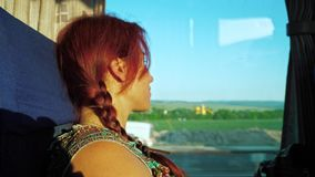 A lonely red-haired traveler girl looks out the bus window at road transport, nature and the blue sky. Summer, sunset time stock video