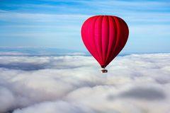 A lonely red hot air balloon floats above the clouds. Concept leader, success, loneliness, victory Royalty Free Stock Photo