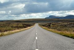 Lonely road. Empty American Highway with mountains in the background Royalty Free Stock Photo