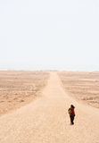 Lonely road. Lonely woman is walking on the desert road royalty free stock images