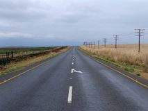 Lonely Road. Public road with burnt grass on the left and telephone lines on the right royalty free stock photos