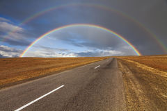 Lonely road in the desert under a rainbow Stock Image