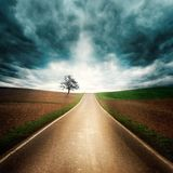 Lonely road with dramatic mood. Lonely and moody road through empty fields with dramatic sky, dark clouds, interesting light and symmetrical composition Stock Image