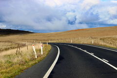 Lonely road between the fields. Lonely australian road between the fields under cloudy sky in winter time Stock Photos