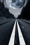 Lonely road with a giant surreal moon stock photo