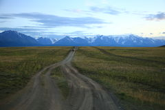 Lonely road leading to the distant Altay Mountains Royalty Free Stock Photos