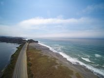 Lonely road between mountain lake and ocean shore. Aerial view Royalty Free Stock Photography