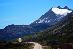 Lonely Road In The Mountains. In the Tundra of the Yukon, just passed the Alaskan border, a lonely road twists and turns through the mountain tops with only the Royalty Free Stock Images