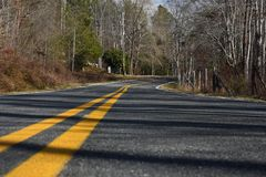 `The Lonely Road` remote country road low perspective. `The Lonely Road` remote country road stock photo by ZDS features trees, shadows, split locust fence royalty free stock photography