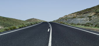 Lonely road in a rural landscape. View of a lonely road in a rural landscape with no traffic stock photos