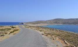 Lonely road and sea, Greece. A lonely road in a desertic area in Crete, Greece Royalty Free Stock Images