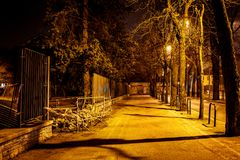 A lonely road with street lamps at night with a fence barrier in an italian village at night. Long time exposure at night stock image