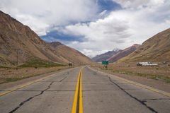 Lonely road surrounded by mountains. Road through the Andes mountains from Argentina to Chile that leads to the Aconcagua National Park Stock Image