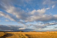 Lonely road under cloudy sky stock images