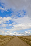 Lonely road under cloudy sky stock photos