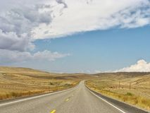 Lonely road. Vanishing point on long lonely road in Wyoming USA stock photos