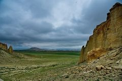 Lonely rocks of the boundless steppe. West Kazakhstan. In the boundless steppe there is a lonely mountain complex Shirkala, which from a distance looks like a stock image