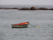 Lonely Row Boat on the Sea. Anchored to Yellow Boy Royalty Free Stock Photography