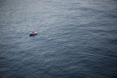 Lonely Rowboat on a Large Expanse of Sea Stock Image