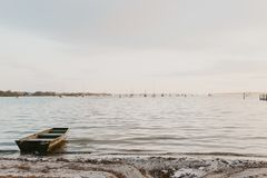 Lonely Rowboat On Peaceful Calm Water Ocean Bay stock photography
