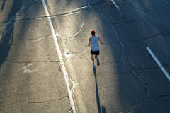Lonely Runner. A lone marathon runner heads towards the rising sun during the opening stages of a race stock images