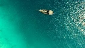 Lonely boat swaying on waves, high noon, aerial. Lonely rustic boat swaying on waves of ocean, on a sunny day, high noon, aerial stock video