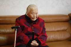 Lonely and sad Asian Chinese 90s old woman. Sad and lonely Asian Chinese old woman, 93 years old, up to 90s , silvery hair, golden earing on her ear Royalty Free Stock Photography