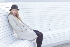 Lonely sad beautiful girl in a black coat and hat, sitting on a white bench cold winter sunny day Royalty Free Stock Photos